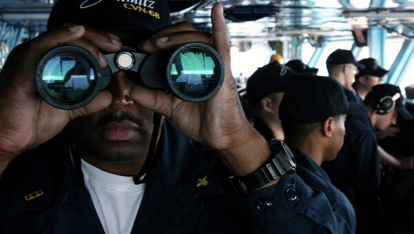 US Navy sailor CW02 Ernest Jackson, 42, of San Diego, California, peers through binoculars from the bridge of the USS Nimitz on Tuesday, June 5, 2007, in the Persian Gulf, where the Nimitz and the USS John C. Stennis aircraft carrier groups are on patrol - Sputnik International