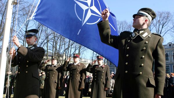 Latvian officers stand guard during the NATO flag rising ceremony in front of the Presidents castle in Riga - Sputnik International
