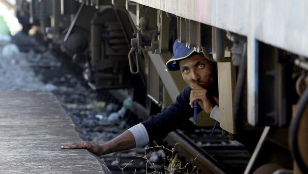 A migrant, hiding under a train, tries to sneak on a train towards Serbia, at the railway station in the southern Macedonian town of Gevgelija, on Monday, Aug. 17, 2015. Over 1,000 migrants from Middle East, Asia and Africa, enter Macedonia daily from Greece, heading north through the Balkans on their way to the more prosperous European Union countries - Sputnik International