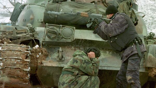A Yugoslav special forces policeman shoots his rifle at opposing Kosovo Liberation Army forces as a Yugoslav Army tank driver covers his ears after coming under fire Tuesday Feb. 23, 1999 in the village of Bukos - Sputnik International