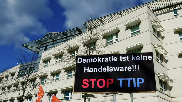 A sign reading Democracy is no trading good, Stop TTIP is lifted in front of the US embassy during a protest against the proposed US-EU free trade pact or Transatlantic Trade and Investment Partnership (TTIP) in Berlin on April 18, 2015 - Sputnik International