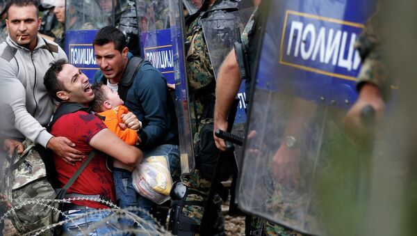 Migrant men help a fellow migrant man holding a boy as they are stuck between Macedonian riot police officers and migrants during a clash near the border train station of Idomeni, northern Greece, as they wait to be allowed by the Macedonian police to cross the border from Greece to Macedonia, Friday, Aug. 21, 2015 - Sputnik International