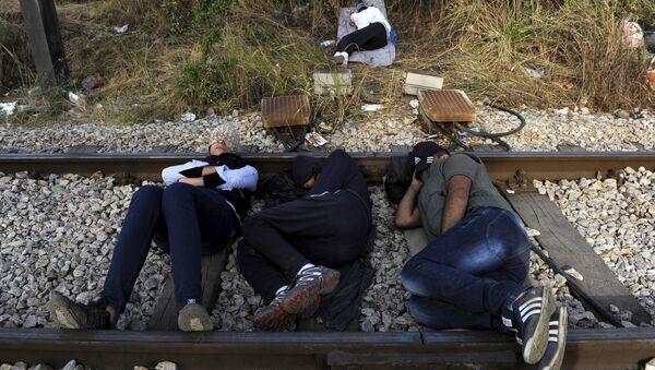 Migrants rest on a railway track at the Greek-Macedonian border, August 21, 2015 - Sputnik International