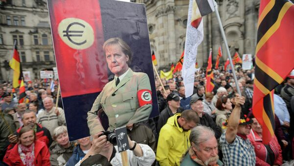 Supporters of the German right-wing movement PEGIDA (Patriotic Europeans Against the Islamisation of the Occident) hold up a poster showing German Chancellor Angela Merkel in a uniform with an Euro-logo-armband as they attend a PEGIDA rally on June 1, 2015 in Dresden, eastern Germany. - Sputnik International
