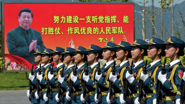 """Chinese female troops practice marching near a billboard showing Chinese President Xi Jinping and the slogan Strive to build a People's Liberation Army that obeys the Party, Wins the war and has outstanding work style"""" at a camp on the outskirts of Beijing, Saturday, Aug. 22, 2015 - Sputnik International"""
