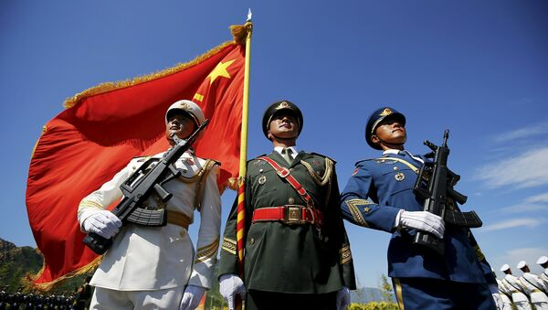 Officers and soldiers of China's People's Liberation Army hold a flag and weapons during a training session for a military parade to mark the 70th anniversary of the end of World War Two, at a military base in Beijing, China, August 22, 2015 - Sputnik International