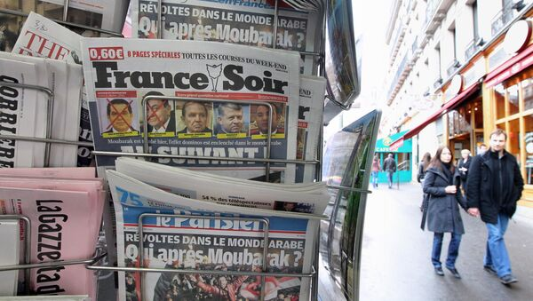People are seen walking behind French daily newspapers displayed at a news kiosk in Paris. (File) - Sputnik International