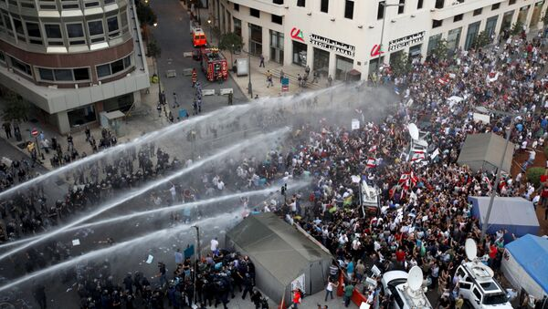 Lebanese protesters are sprayed with water during a protest against corruption and rubbish collection problems near the government palace in Beirut - Sputnik International