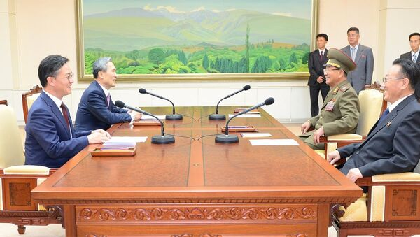 South Korean National Security Adviser Kim Kwan-jin (2nd L), South Korean Unification Minister Hong Yong-pyo (L), Secretary of the Central Committee of the Workers' Party of Korea Kim Yang Gon (R), and Hwang Pyong-so (2nd R), the top military aide to the North's leader Kim Jong Un, talk during the inter-Korean high-level talks at the truce village of Panmunjom inside the Demilitarized Zone separating the two Koreas, in this picture provided by the Unification Ministry and released by Yonhap on August 25, 2015 - Sputnik International