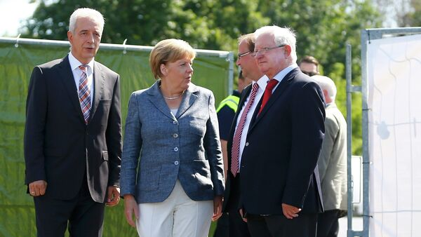 Saxony State Prime Minister Stanislaw Tillich, German Chancellor Angela Merkel, major Juergen Opitz and President of the German Red Cross Rudolf Seiters (LtoR) arrive to visit an asylum seekers accomodation facility in the eastern German town of Heidenau near Dresden, August 26, 2015 where last week more than 30 police were injured in clashes, when a mob of several hundred people pelted officers with bottles and fireworks - Sputnik International