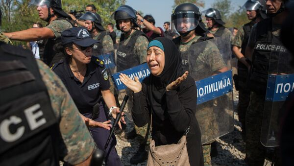 A Syrian refugee cries after she lost her daughter during clashes between Macedonian police and refugees who try to cross the borders in the town of Idomeni, Northern Greece, on Wednesday, Aug. 26, 2015. - Sputnik International