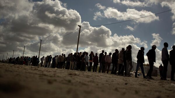 Migrants line up as the wait for a food ration distributed by the Banque Alimentaire of Calais at a camp in northern France, Tuesday, Aug. 4, 2015 - Sputnik International