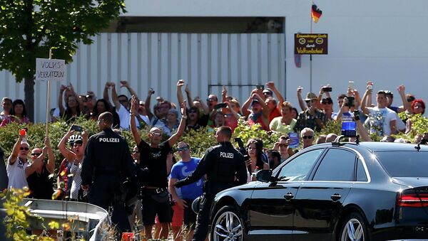 People hold a placard reading Traitor as German Chancellor Angela Merkel leaves after her visit to an asylum seekers accomodation facility in the eastern German town of Heidenau near Dresden, August 26, 2015 where last week more than 30 police were injured in clashes, when a mob of several hundred people pelted officers with bottles and fireworks - Sputnik International