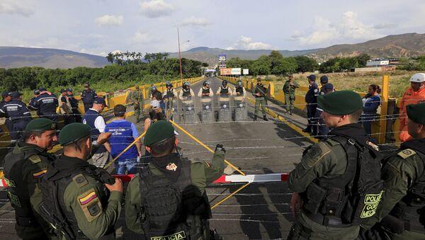 Colombian policemen stand guard in front of the border with Venezuelan policemen Bolivarianos near Villa del Rosario village, August 27, 2015 - Sputnik International