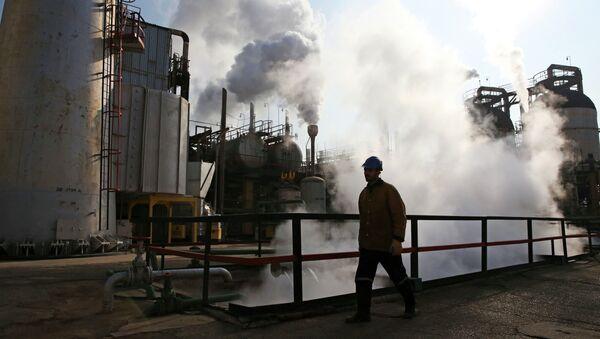 An Iranian oil worker walks in Tehran's oil refinery south of the capital Tehran, Iran, Monday, Dec. 22, 2014 - Sputnik International