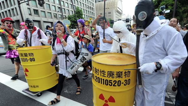 Protesters wearing gas masks and white costumes similar to those of decontamination workers at the crippled Fukushima plant beat drums painted with radioactive waste symbols during an anti nuclear power demonstration march in Tokyo on July 29, 2012 - Sputnik International