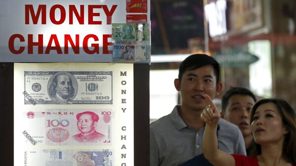 People look at the exchange rate at a moneychanger displaying a poster of U.S. dollar bill, Chinese Yuan and Malaysia Ringgit in Singapore - Sputnik International