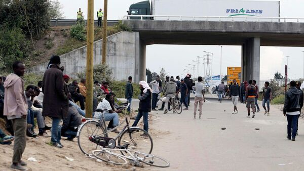 Migrants stand near a highway overpass near the makeshift camp called The New Jungle in Calais, France. - Sputnik International