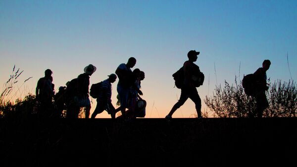 A group of refugees walk on the railway tracks after crossing from Serbia, into Roszke, Hungary, Tuesday, Sept. 1, 2015. - Sputnik International