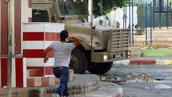 A Palestinian throws a stone toward an Israeli vehicle during clashes with Palestinians in an early morning operation in the West Bank city of Jenin, Wednesday, July 2, 2014. - Sputnik International