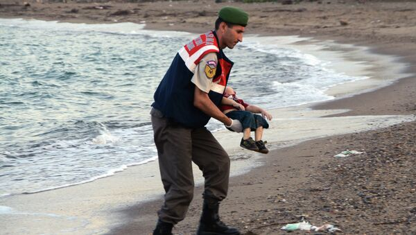 A paramilitary police officer carries the lifeless body of an unidentified migrant child, lifting it from the sea shore, near the Turkish resort of Bodrum, Turkey, early Wednesday, Sept. 2, 2015. - Sputnik International