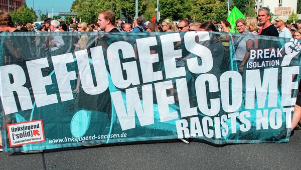 Protesters demonstrate with a banner 'Refugees welcome!' in Dresden, eastern Germany, Saturday, Aug. 29, 2015. A refugee shelter was attacked by far-right protesters in Heidenau near Dresden over the last weekend. - Sputnik International