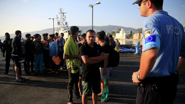 A migrant waits in line next to a Frontex officer (R) at the port of Kos, following a rescue operation off the Greek island of Kos, August 14, 2015 - Sputnik International