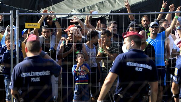 Migrants watch from behind a fence as Hungarian riot police stands guard in front of a migrant reception centre in Roszke, Hungary, September 4, 2015 - Sputnik International