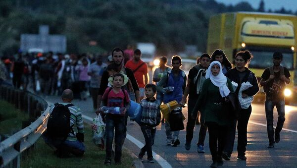 People walk in a long line along the highway near Budapest, Hungary, heading for the Austrian border. - Sputnik International