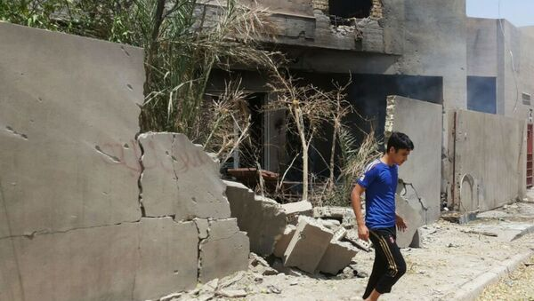 Abdullah Ahmed walks outside his home that was damaged in a bombing in Fallujah, Iraq. The U.S. and its coalition allies have carried out more than 1,000 strikes in Iraq since its campaign began in August - as well as hundreds more by American and Arab air forces in neighboring Syria. - Sputnik International