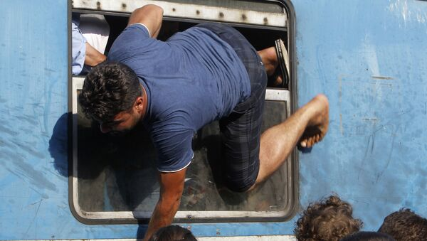 A migrant tries to board a train towards Serbia through a window, at the railway station in the southern Macedonian town of Gevgelija, on Saturday, Aug. 15, 2015 - Sputnik International