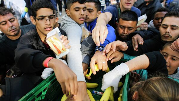 Migrants grab for food delivered by volunteers as they wait for registration at the reception center for refugees and asylum seekers in Berlin, Germany, Friday, Sept. 4, 2015 - Sputnik International
