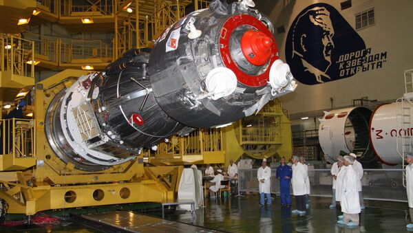 Specialists of RSC Energia work to install the payload shroud on a manned Soyuz TMA-02M spacecraft in the assembly and test complex at Baikonur Cosmodrome, where work proceeds on building a Soyuz-FG space rocket - Sputnik International