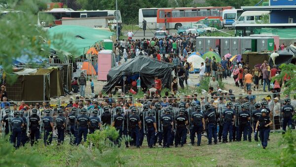 Police officers guard a local refugee camp in the village of Roszke at the Serbian-Hungarian border on September 4, 2015 where migrants are being held - Sputnik International