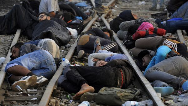 Refugees and migrants sleep on the railway tracks close to the borders of Greece with Macedonia, near the village of Idomeni, September 6, 2015 - Sputnik International
