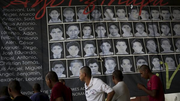 Newly enrolled students stand near a banner showing the photographs of the 43 missing students of the Ayotzinapa teachers' training college, at the college in Tixtla, on the outskirts oft Chilpancingo, in the Mexican state of Guerrero, August 16, 2015 - Sputnik International