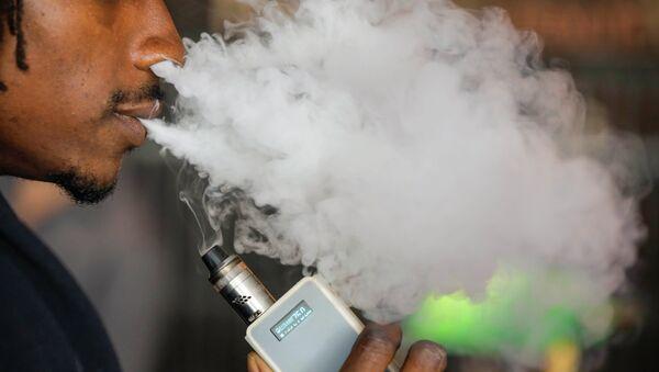 A man smokes an electronic cigarette vaporizer, also known as an e-cigarette, in Toronto, August 7, 2015 - Sputnik International