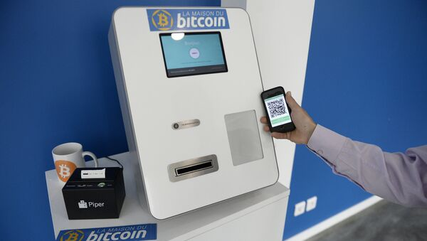 This picture taken on June 20, 2014, shows a man placing his phone next to a Bitcoins (virtual currency) dispenser at La Maison du Bitcoin in Paris. - Sputnik International