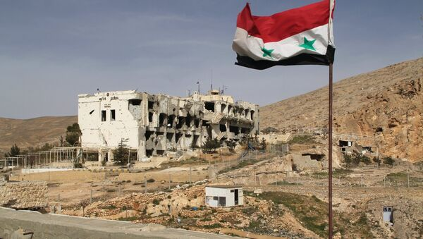 A Syrian flag on the background of ruined houses in the Syrian town of Maaloula, 55 km from Damascus, which was twice captured and looted by Jabhat al-Nusra militants. - Sputnik International