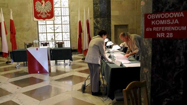 A woman takes her ballot paper during a referendum asking people to vote on changing the voting system, the funding of political parties and taxation rules, in Warsaw, Poland, September 6, 2015. - Sputnik International