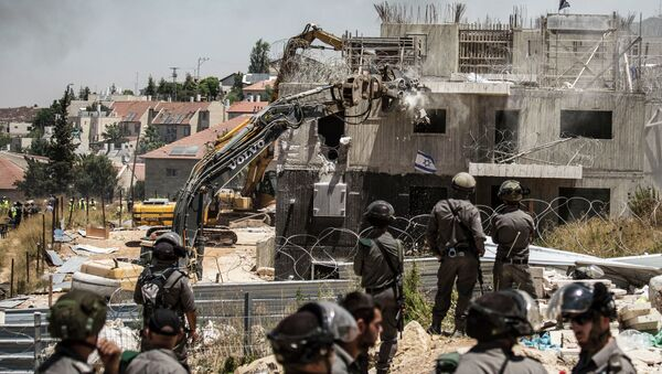 Israeli officers from the Border Patrol watch over the demolition of a building at the Jewish settlement of Beit El, near the West Bank town of Ramallah, Wednesday, July 29, 2015. - Sputnik International