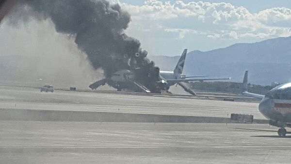 In this photo taken from the view of a plane window, smoke billows out from a plane that caught fire at McCarren International Airport, Tuesday, Sept. 8, 2015, in Las Vegas. An engine on the British Airways plane caught fire before takeoff, forcing passengers to escape on emergency slides. - Sputnik International