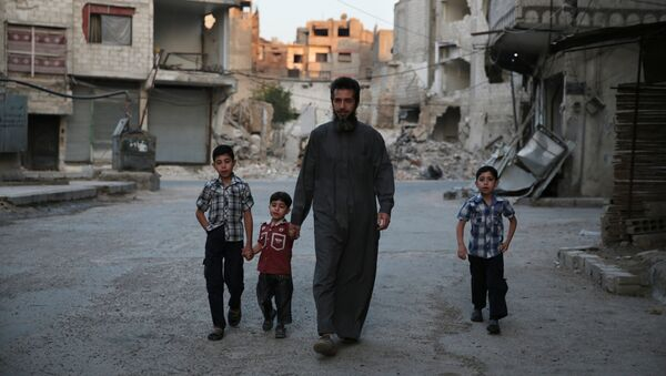 A Syrian man heads to a mosque with children in the rebel-held area of Douma, east of the capital Damascus - Sputnik International
