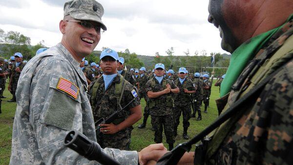 An unidentified US military (L) says goodbye to a Honduran soldier. - Sputnik International