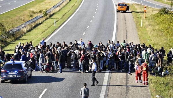 A group of refugees and migrants who were walking north stand on the highway in southern Denmark on Wednesday, Sept. 9, 2015 - Sputnik International