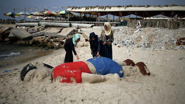 Palestinian girls put flowers on a sand sculpture depicting Syrian boy Aylan Kurdi, a three-year-old boy who drowned off Turkey, on September 7, 2015, on Gaza city beach - Sputnik International