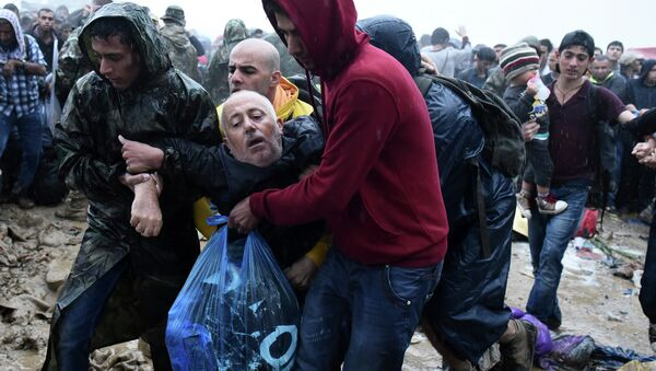 Migrants help an elderly man to pass from the northern Greek village of Idomeni to southern Macedonia, Thursday, Sept. 10, 2015. Thousands of people, including many families with young children, braved torrential downpours to cross Greeceís northern border with Macedonia early Thursday, after Greek authorities managed to register about 17,000 people on the island of Lesbos in the space of a few days, allowing them to continue their journey north into Europe. - Sputnik International