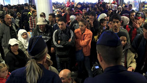 Migrants, who mostly crossed into the country from Serbia and are hoping to make their way to Austria, wait for trains heading to Hegyeshalom or Gyor, in a transit area at Keleti station in Budapest, Hungary, September 12, 2015 - Sputnik International