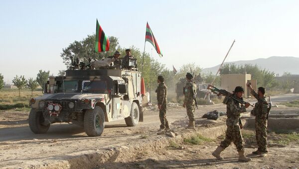 Afghan national army stand guard near the dead body of a Taliban attacker in front of the main prison building after an attack in Ghazni province, eastern Afghanistan, Monday, Sept. 14, 2015 - Sputnik International