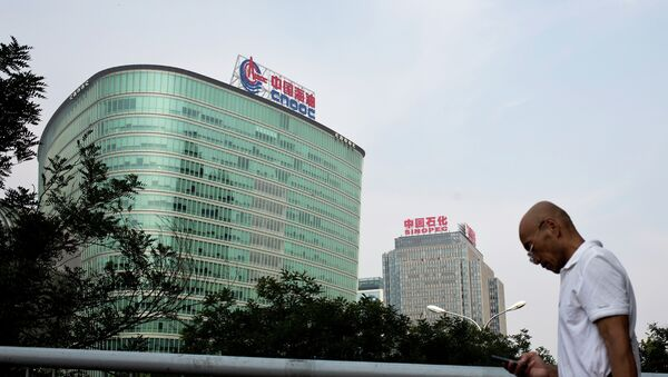 A man checks his mobile phone as he walks by buildings of China's state-owned companies, China National Offshore Oil Corp. (CNOOC), left, and China Petroleum & Chemical Corp. (Sinopec), in Beijing Monday, Sept. 14, 2015 - Sputnik International